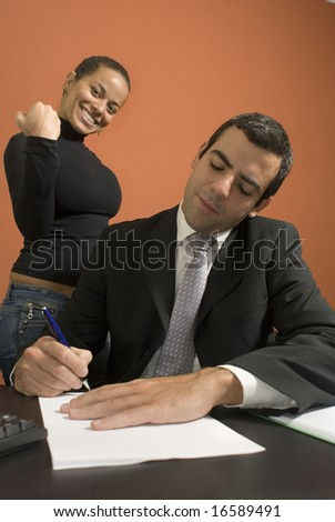 Businessman working at his desk while his co-worker pretends to be angry with him. Vertically framed photo - stock photo