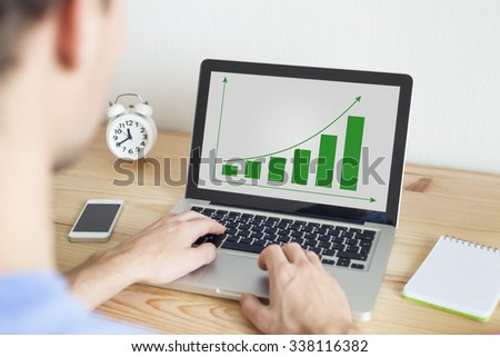 Businessman working at home on laptop and smartphone on sustainable development project - stock photo