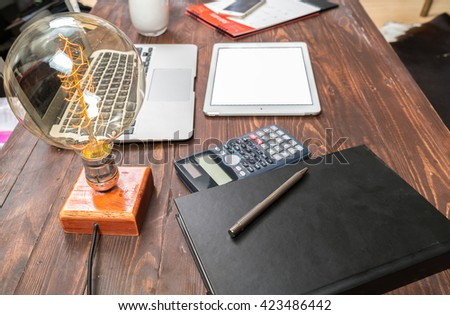 Businessman working at office desk and signing a document, computers and paperwork all around, top view      - stock photo