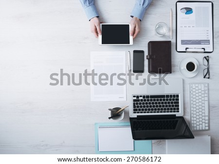 Businessman working at office desk and using a digital touch screen tablet hands detail, computer and objects on the right, top view