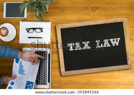 Businessman working at office desk and using computer and objects, coffee, top view, TAX LAW  concept - stock photo