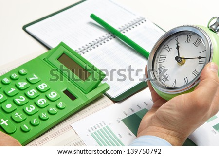 Businessman working in the office. The alarm-clock - stock photo
