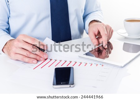 Businessman working on a digital tablet and analyzing column charts. - stock photo