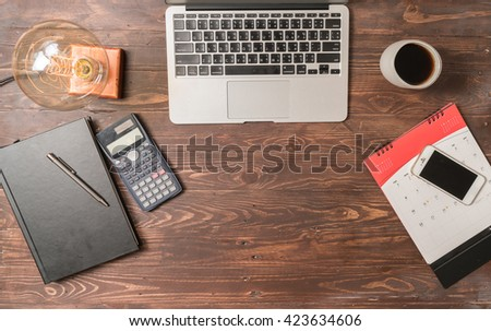 Businessman working on a laptop at office desk with paperwork and other objects around, top view