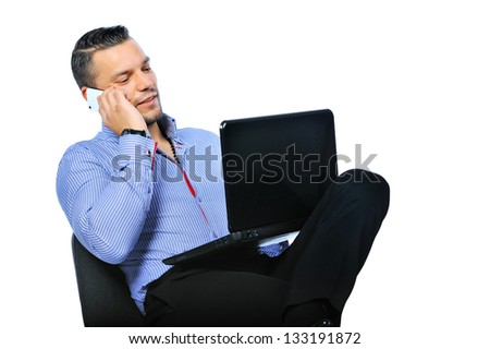 Businessman working on a notebook computer while talking on a mobile phone - stock photo