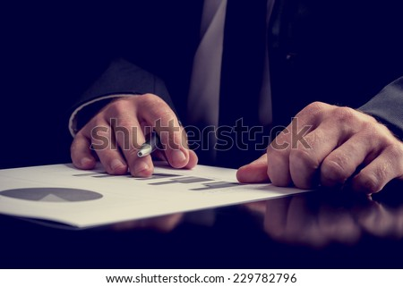 Businessman working on a presentation or performance analysis making notes on a set of bar and pie graphs, close up view of his hands as he sits at a desk.