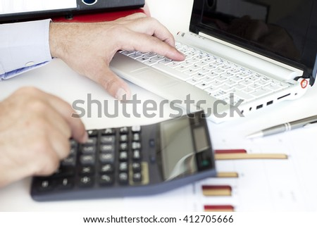 Businessman working on computer and calculator in the office