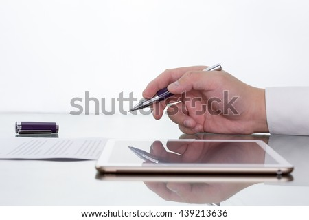 Businessman working on digital tablet on his desk with hand holding pen reflection.