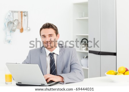 Businessman working on his laptop at home - stock photo