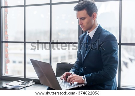 Businessman working on his laptop computer sitting in office - stock photo
