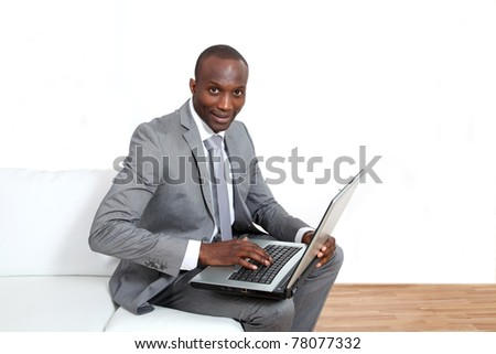 Businessman working on laptop in waiting room