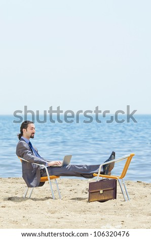 Businessman working on laptop on seaside