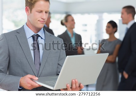 Businessman working on laptop with colleagues behind him in the office - stock photo