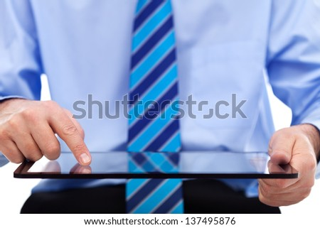 Businessman working on tablet computer - closeup on device and hands, copyspace - stock photo