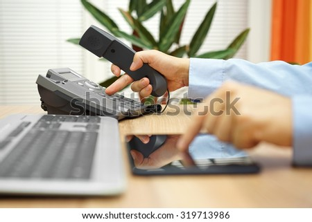 businessman working on tablet computer  is calling service for support - stock photo