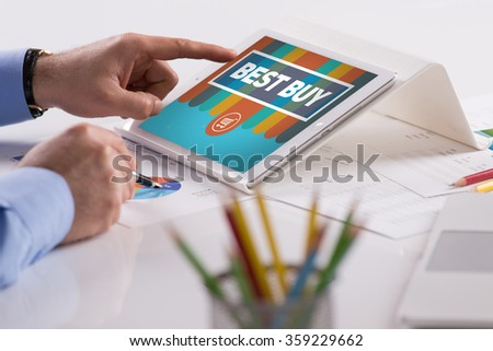 Businessman working on tablet with BEST BUY on a screen