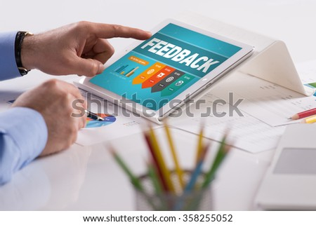 Businessman working on tablet with FEEDBACK on a screen - stock photo