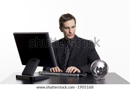 Businessman working on the computer with an earth globe on his desk. - stock photo