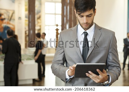 Businessman working on the digital tablet with his office in the background - stock photo