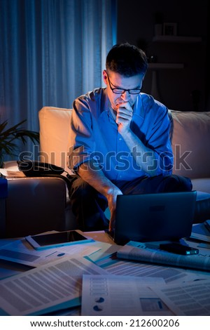 Businessman working overtime on laptop at home on sofa until late. - stock photo