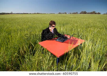 Businessman working remotely from his office in the field, using mobile and wireless technology.