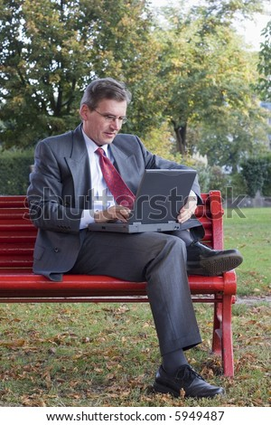 Businessman working with a laptop while sitting on a red bench in a park - stock photo
