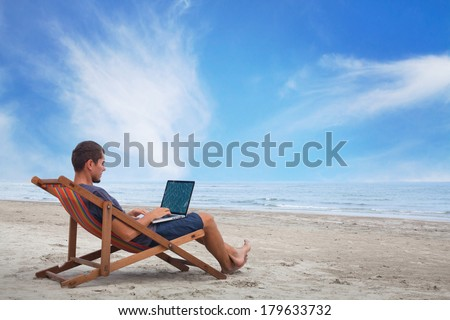 businessman working with computer on the beach - stock photo