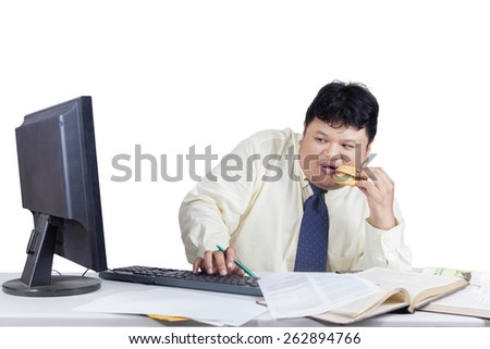 Businessman working with computer while eating burger and looks scared when looking the monitor - stock photo