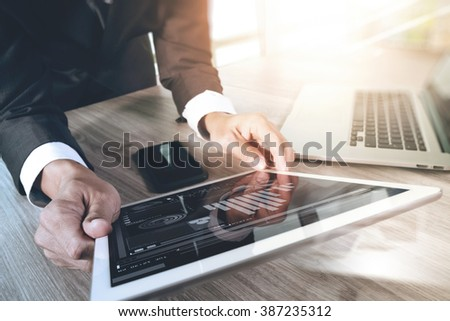 businessman working with digital tablet computer and smart phone and laptop computer with digital business strategy layer effect on wooden desk as concept - stock photo