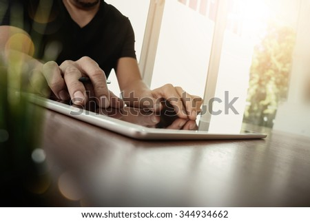 businessman working with digital tablet computer on wooden desk with green plant foreground as concept - stock photo