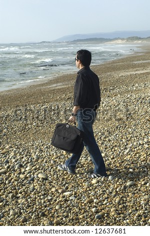 businessman working with folder in hand, moving towards the sea - stock photo
