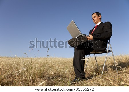 businessman working with his laptop outside in the field - stock photo