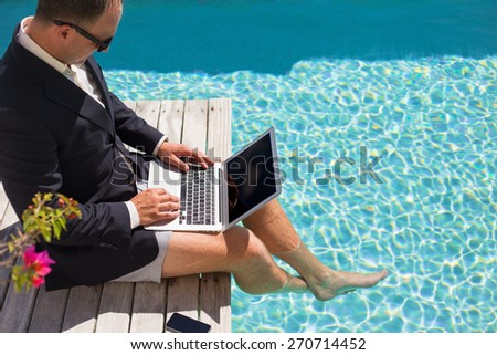 Businessman working with laptop computer by the pool - stock photo