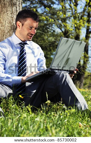 businessman working with laptop in a park in summer - stock photo