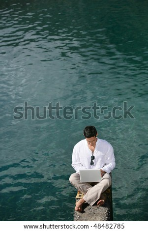 Businessman working with laptop on a pontoon - stock photo