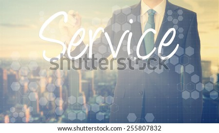 businessman write on transparent board Service with sunset over the city in the background, the sun's rays falling into lens are symbolizing the good attitude - stock photo