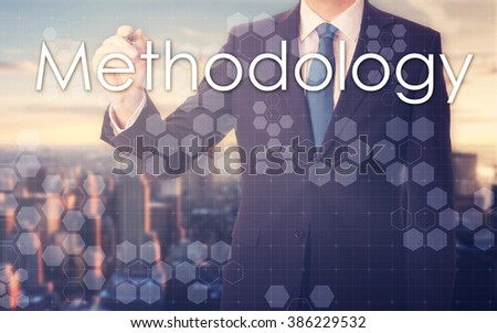 businessman writes on board text: Methodology - with sunset over the city in the background - stock photo