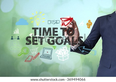Businessman writing and drawing TIME TO SET GOALS concept on blurred abstract background , business concept , business idea - stock photo