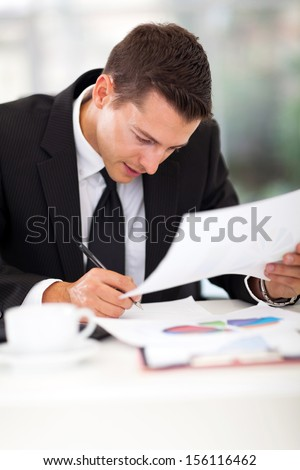 businessman writing at his desk in the office - stock photo