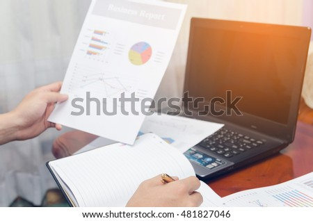 businessman writing book with document chart and laptop on wood table