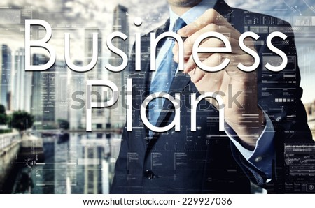 Businessman writing Busines Plan on virtual screen behind the back of the businessman one can see the city behind the window - stock photo