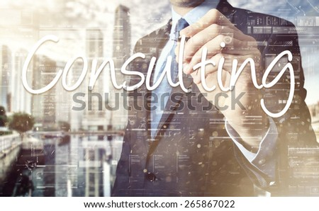 Businessman writing Consulting on virtual screen behind the back of the businessman one can see the city behind the window - stock photo