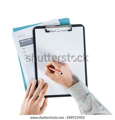 Businessman writing down notes on a  blank clipboard and financial reports, hands close up, top view