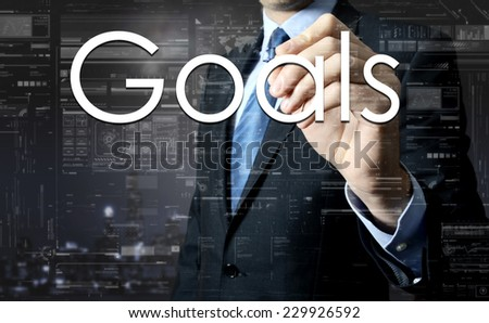 Businessman writing Goals on virtual screen behind the back of the businessman one can see the city behind the window - stock photo