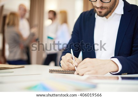 Businessman writing in his notepad in office - stock photo