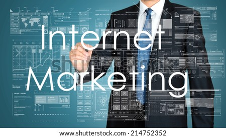 businessman writing Internet Marketing and drawing graphs and diagrams on green background