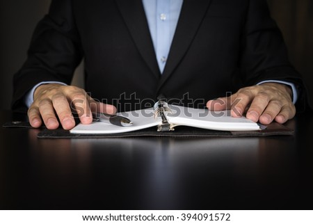 Businessman writing investment idea on book - stock photo