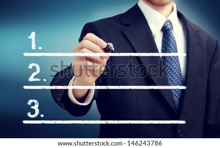 Businessman writing lists with navy blue background - stock photo