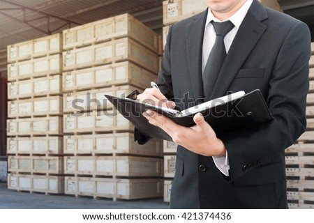 Businessman writing notebook with blurred cargo in wooden case at warehouse background - stock photo