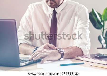 Businessman writing notes and using laptop, working overtime at office desk, multitasking and project deadline concept, retro toned image, selective focus - stock photo